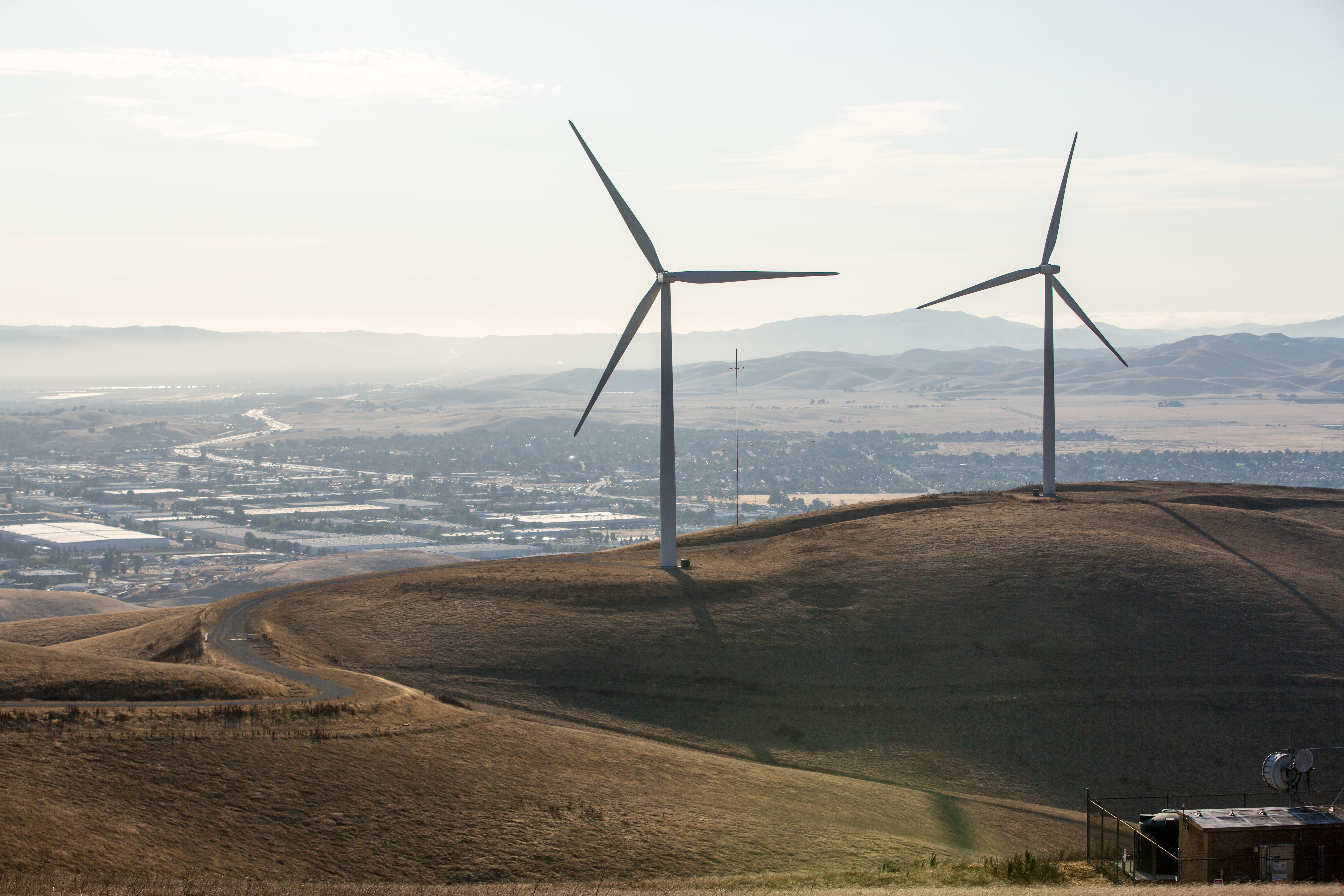 two wind turbines on a hill overlooking a town