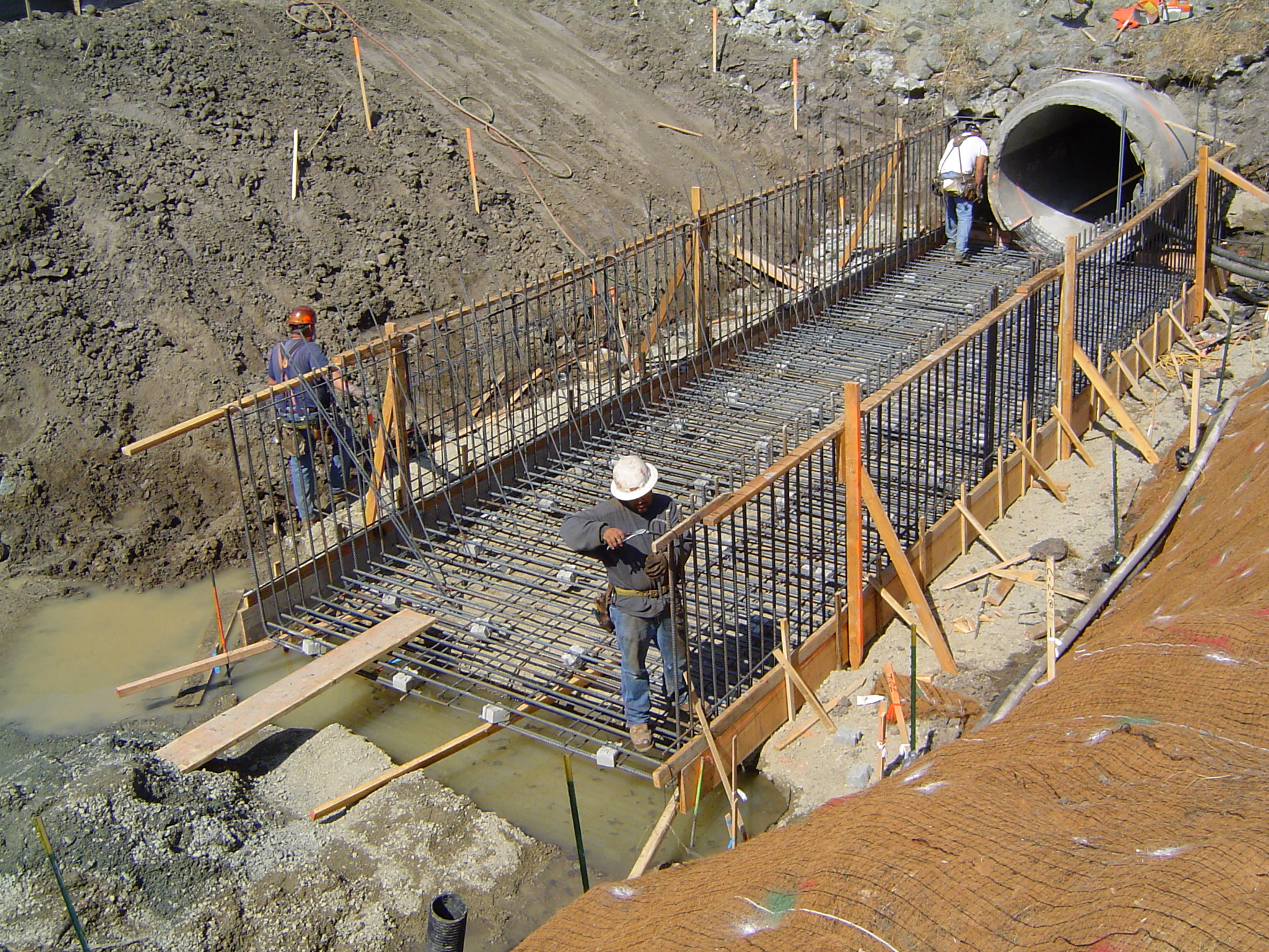 Workers building a support structure for a drainage culvert