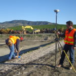 Surveyors at a construction site driving stakes